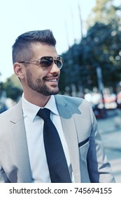 Portrait of young successful businessman outdoor walking on street wearing sunglasses.