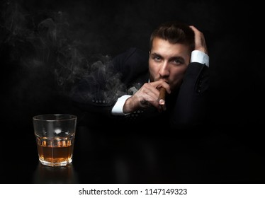 Portrait of a young and successful businessman smoking a cigar and drinking a whiskey in front of a black background