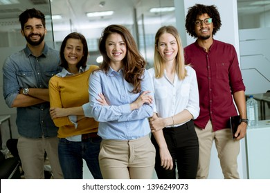 Portrait of young successful creative business team looking at camera and smiling in the office