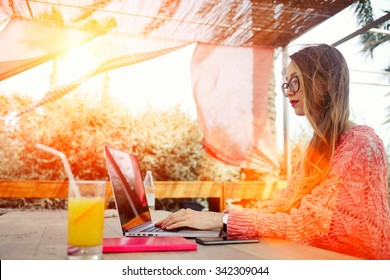 Portrait of a young successful female freelancer using net-book for distance work during morning breakfast, attractive woman keyboarding on laptop computer while sitting in sidewalk cafe in summer day
