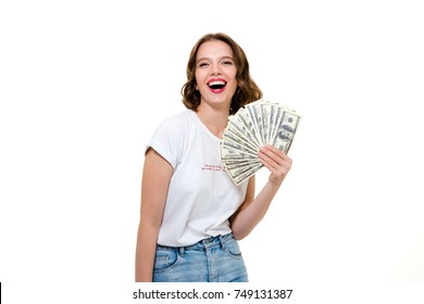 Portrait of a young successful girl holding bunch of money banknotes and looking at camera isolated over white background