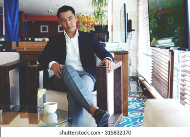 Portrait of a young successful managing director watching news on TV while waiting for business partners in modern restaurant, confident intelligent business men relaxing in cafe during lunch break