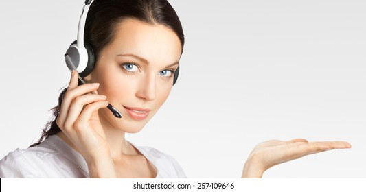 Portrait of young support phone operator in headset showing something or blank copyspace area for text or slogan, over grey