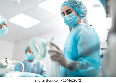 Portrait of young surgical nurse in sterile glove holding respiratory equipment for patient. Focus on lady face in protective mask