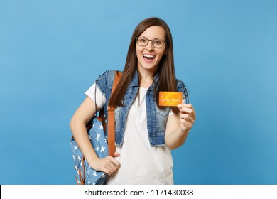 Portrait of young surprised excited pretty woman student in denim clothes, glasses with backpack holding credit card isolated on blue background. Education in high school university college concept