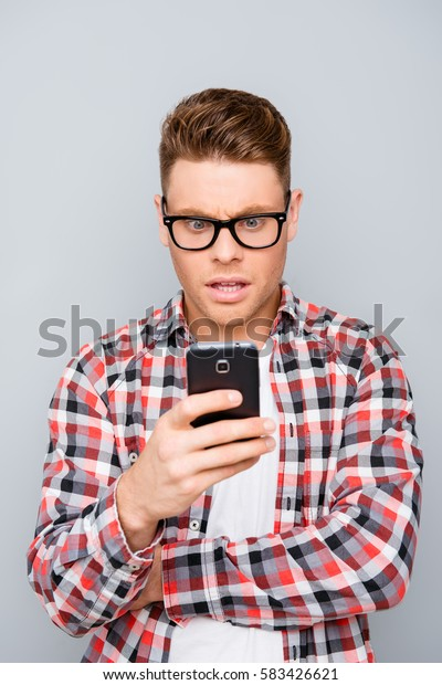 Portrait of young  surprised guy on gray background texting a message on his smartphone