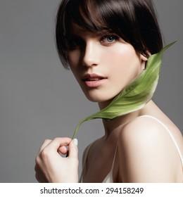 Porträt eines jungen, süßen Mädchens im Studio auf grauem Hintergrund mit einer grünen Blume in der Hand, das Konzept von Schönheit und Gesundheit