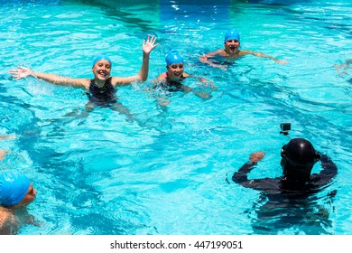 Portrait of young swimmers posing at action camera in swimming pool. Diver with wetsuit and small video camera on stick shooting sport footage.
