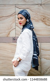 Portrait of a young, tall and elegant Muslim woman wearing a headscarf (tudung hijab) over her modern white outfit against a plain marble background. She is fashionable and attractive.