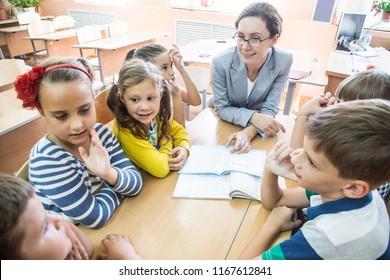 portrait of young teacher with children in elementary school