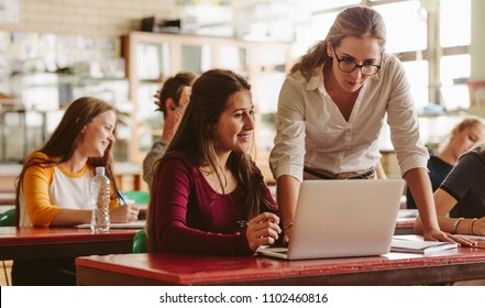 Portrait of young teacher helping a student during class. University student being helped by female lecturer during class.