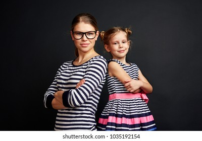 Portrait of young teacher with little pupil standing with crossed arms at blackboard.