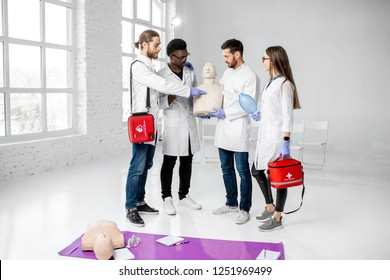 Portrait of a young team of medics in uniform standing together with medical stuff after the first aid training in the white classroom