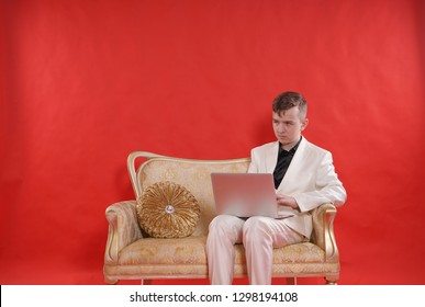 portrait of a young teen man wearing white office suit and sitting on the golden luxury sofa on red background. he works on the laptop and think about his future profession while studying.
