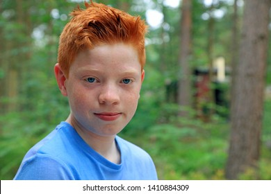 Portrait Of A Young Teenage Boy With Ginger Hair And Blue Eyes.