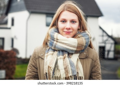 Portrait of young teenage girl with long blond hair outside house