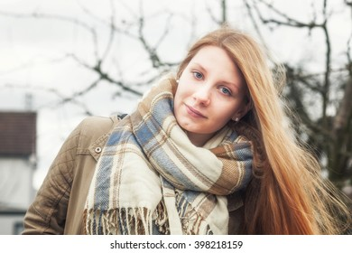 Portrait of young teenage girl with long blond hair outdoors