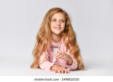 Portrait of a young teenage girl in a long-sleeved Roh dress and matching tone gumshoes lying on the floor, isolated on a white background. Looking away