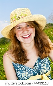 Portrait of young teenage girl smiling on summer meadow in straw hat