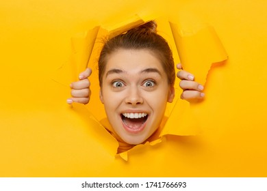 Portrait of young teenage girl tearing paper with hands and looking through it with amazed face and round eyes, isolated on yellow background