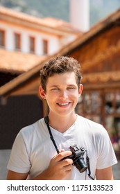 Portrait of a young teenage male holding a camera outdoors smiling. Blurred buildings in the background.
