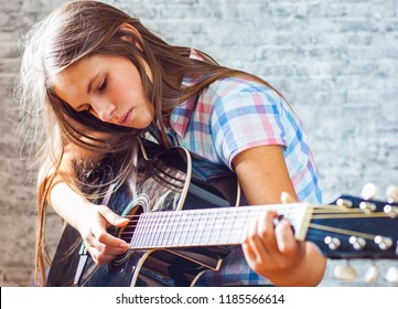 portrait of young teenager brunette girl with long hair playing an black acoustic guitar on gray wall background