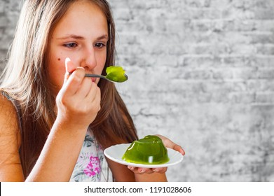portrait of young teenager brunette girl with long hair eating delicious green kiwi jelly dessert on gray wall background