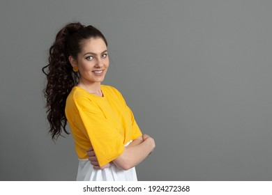 portrait of a young teenager with long wavy hair dressed in a yellow t-shirt, isolated on gray