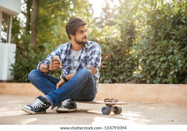 Portrait of a young teenager sitting on the long board.