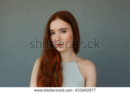 Portrait Of Young Tender Redhead Teenage Girl With Green Eyes Wearing Blue Top Looking At Camera