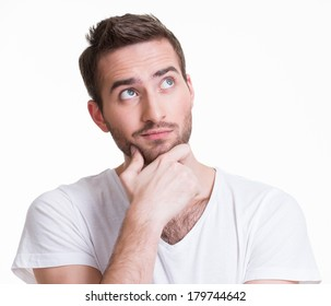 Portrait of the young thinking man looks up in casuals isolated on white background.