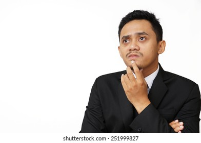 Portrait of the young thinking man looks up with hand near face - isolated on white