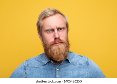 Portrait of young thoughtful man look seriously on camera. Calm peaceful guy with blond hair and red beard look scowl. Isolated on yellow background