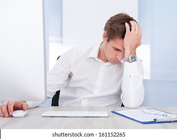 Portrait Of Young Tired Businessman Sitting In Office