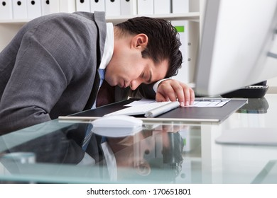Portrait Of A Young Tired Businessman Sleeping At Desk
