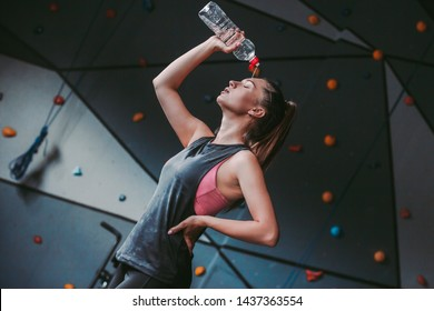 Portrait of young tired sweaty fitness girl drinking water from bottle while standing in dark gym. Beautiful wet sports woman pouring water on her body after hard workout training. Sexy athlete girl