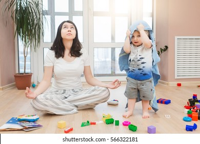 Portrait of young tired yoga mom spending time with her little baby boy, relaxing while her kid son playing games, throw toys and arrange a mess at home