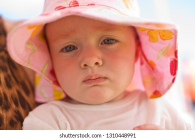 Portrait of a young toddler wearing a floral sunhat while outside.