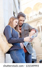 Portrait of a young tourist couple standing together in a destination city holding and looking at a street map while on vacation.
