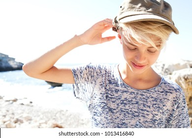 Portrait of young tourist teenager male on rocky beach holiday, looking down smiling wearing baseball cap, shading, sunshine sea sunny vacation, outdoors. Healthy recreation lifestyle, adventure.