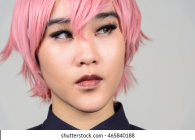 Portrait of young transgender person wearing pink wig