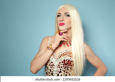 Portrait of young transgender woman in bright costume on color background