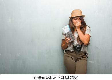 Portrait of young traveler latin woman against a wall biting nails, nervous and very anxious and scared for the future, feels panic and stress. Holding her passport and boarding pass.