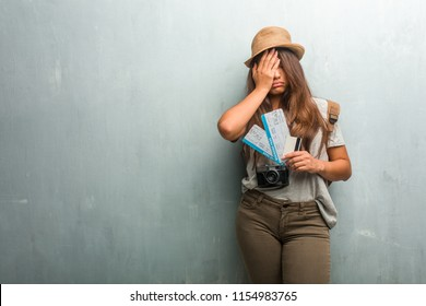 Portrait of young traveler latin woman against a wall worried and overwhelmed, forgetful, realize something, expression of shock at having made a mistake. Holding boarding pass and a credit card.