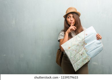 Portrait of young traveler latin woman against a wall keeping a secret or asking for silence, serious face, obedience concept. Holding a city map.