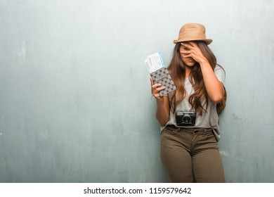 Portrait of young traveler latin woman against a wall feels worried and scared, looking and covering face, concept of fear and anxiety. Holding her passport and boarding pass.