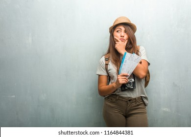 Portrait of young traveler latin woman against a wall doubting and confused, thinking of an idea or worried about something. Holding a boarding pass.