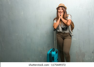 Portrait of young traveler latin woman against a wall surprised and shocked, looking with wide eyes, excited by an offer or by a new job, win concept. Holding a blue suitcase.