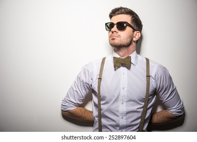 Portrait of young trendy man with black glasses, suspenders and bow-tie on gray background.