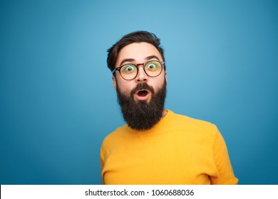 Portrait of young trendy person in eyeglasses looking excited and surprised at camera on blue.